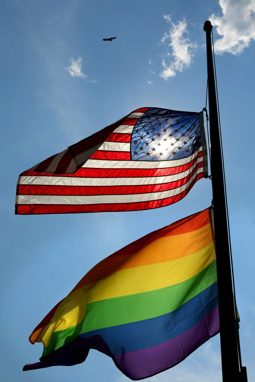 A pride flag flies alongside an American flag.