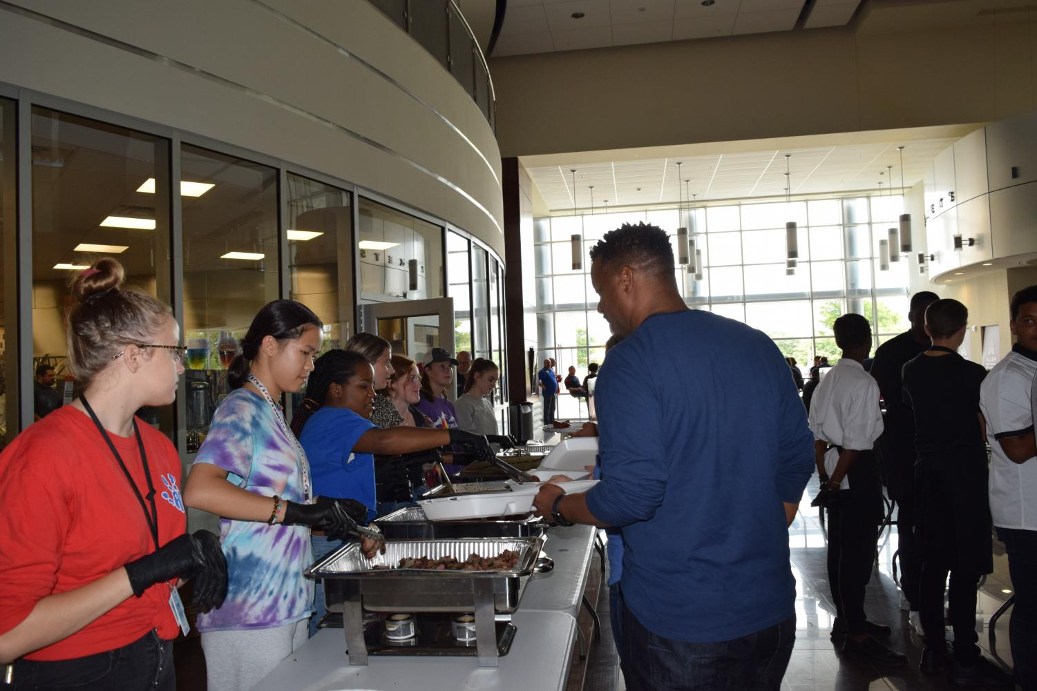 Blú students serve barbecue to staff members.