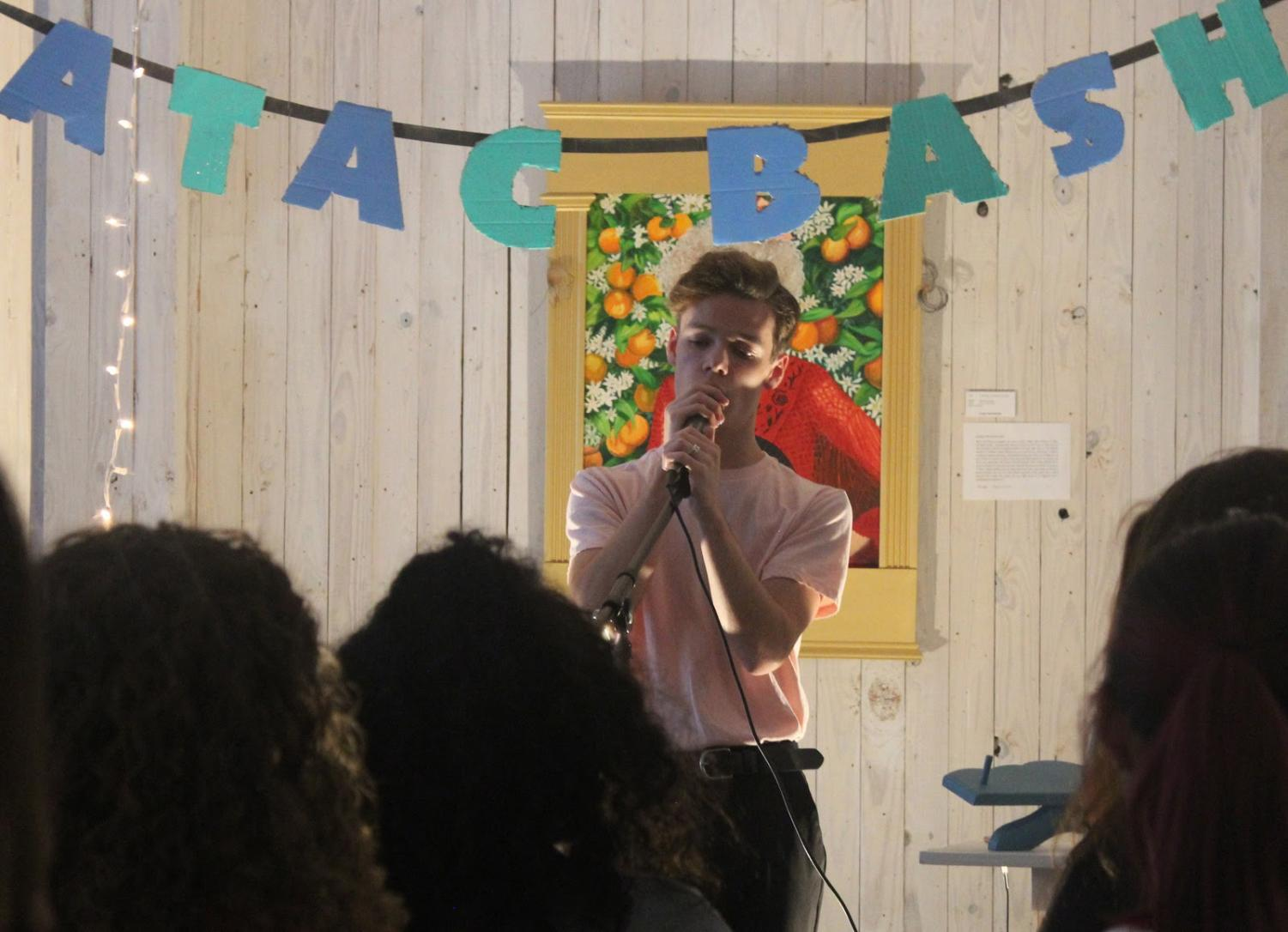 Senior Levi Reeves sings into his microphone as he performs in front of a crowd of fellow musicians at the August ATAC Bash. Performers display their musical skills at ATAC bashes and engage in an artistic community in the process.