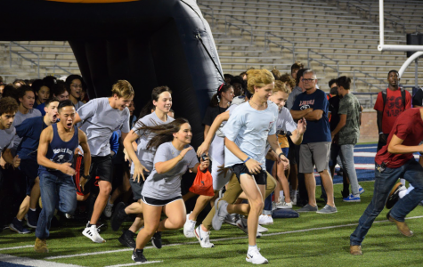 """The swim team runs out to the field onto of the football stadium-. """"I think the pep rally was a great idea""""  Junior Ansh Chawla said. """"A family event that brought a lot of sports teams together. I think it went really well."""" All the sports teams ran out to the field to be cheered for by the community."""