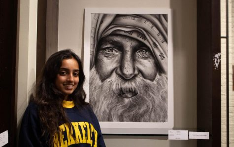 "Nikki Shah poses with her charcoal piece, ""Old Man."" ""I wanted to do a piece that connected to my heritage,"" said Shah. Her piece ended up winning third place and stands out with its careful detail."