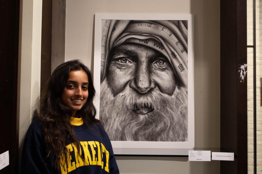 """Nikki Shah poses with her charcoal piece, """"Old Man."""" """"I wanted to do a piece that connected to my heritage,"""" said Shah. Her piece ended up winning third place and stands out with its careful detail."""