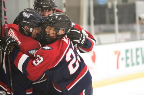 Teammates #4 Robert Bernier, #23 Simon Minsang Kim, and #34 Patrick Mccracken celebrate after a goal is scored.